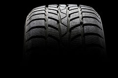 Studio shot of a black car tire. In a dark ambient on black background Royalty Free Stock Images