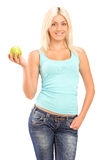 A studio shot of a blond smiling woman holding a green apple and Royalty Free Stock Photos