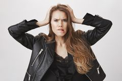 Studio shot of bothered and confused attractive female in leather jacket holding hands on head, biting lip and frowning. Being puzzled, having problem or issue royalty free stock image