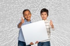Studio shot of a boy and girl holding white plastic for writing ads or copy space against grey backgrounf with extrusion shot of a. Studio shot of a young boy stock photography