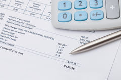 Studio shot of calculator and pen over some receipt under it - focus on pen Royalty Free Stock Image