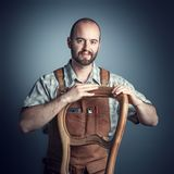 Studio shot of carpenter. Carpenter with unfinished chair, studio shot portrait stock image