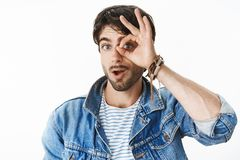 Studio shot of charismatic and joyful handsome european man with blue eyes showing zero or null with circle over eye and. Peeking through it as being amazed stock images
