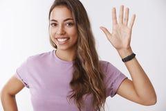 Studio shot charming friendly outgoing fair-haired woman volunteering wanna take part university activity raising hand. Waving smiling broadly saying hi stock photos