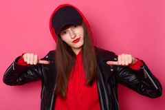 Studio shot of cheeky cool young girl dressed in comfortable red hoody, leather jacket, black cap, points with thumb, being in. Good mood, being photographed in royalty free stock photo