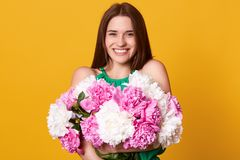 Studio shot of cheerful bright girl, looks happy, stands with toothy smile, brunette young woman holding bouquet of white and pink. Peonies, expresses happyness stock images