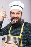 Studio shot of a chef with beard blinking and tasting  soup with Stock Image