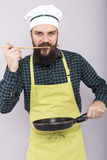Studio shot of a chef with beard tasting the food with a wooden Royalty Free Stock Image
