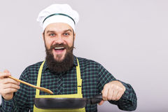 Studio shot of a chef with beard tasting the food with a wooden Royalty Free Stock Images