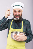 Studio shot of a chef with beard tasting  soup with a ladle Stock Images