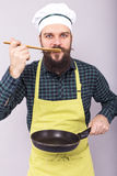 Studio shot of a chef  tasting the food with a wooden spoon Stock Photography