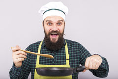 Studio shot of a chef  tasting the food with a wooden spoon Royalty Free Stock Photography