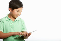 Studio Shot Of Chinese Boy With Digital Tablet Stock Photos