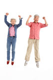 Studio Shot Of Chinese Senior Couple Jumping Royalty Free Stock Photography