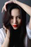 Studio shot, close up face of beautiful asian woman model black. Hair and red lips stock photography