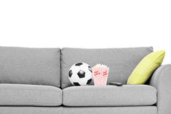 Studio shot of a couch with soccer ball and popcorn box on it Stock Photos