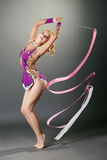 Studio shot of curved gymnast dancing with ribbon Royalty Free Stock Image