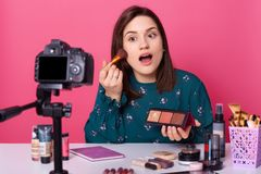 Studio shot of cute young Caucasian woman blogger, advertising new beauty products for her followers, online translation, using royalty free stock photos