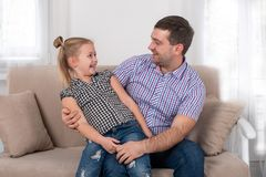 Studio shot of a little girl and her dad cheerfully sitting on the sofa at home and looking each other stock photo
