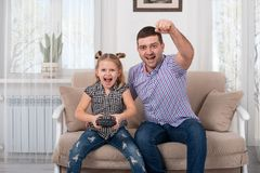 Studio shot of a little girl and her dad sitting on the sofa at home with the joystick and together emotionally playing a game royalty free stock photos