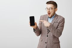 Studio shot of delighted amused funny bearded guy in glasses and stylish jacket holding smartphone pointing at device. Screen joyful and thrilled smiling with royalty free stock images