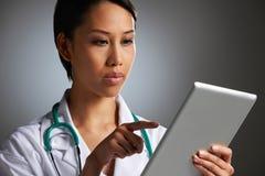 Studio Shot Of Doctor Using Digital Tablet Stock Photos
