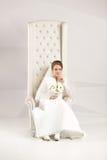 Studio shot of elegant bride posing at luxurious chair Stock Photos