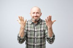 Studio shot of excited over-emotive mature man pulling hands towards camera and arguing or showing regret. Over gray background stock photography
