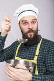 Studio shot of an expressive chef with beard tasting  soup with Royalty Free Stock Images