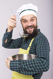 Studio shot of an expressive chef with beard tasting  soup with Royalty Free Stock Photography