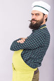 Studio shot of a fat bearded man with apron and cook hat Royalty Free Stock Image