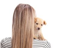 Studio shot of a female from behind hugging a puppy on her shoulder royalty free stock photo