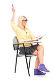 A studio shot of a female student raising her hand Royalty Free Stock Photography