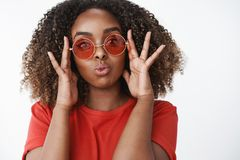 Studio shot of flirty and feminine attractive african-american woman in red t-shirt and stylish round sunglasses folding. Lips in cute glamour way and touching royalty free stock photos