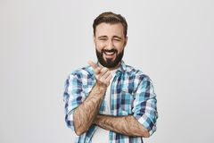 Studio shot of funny bearded man in trendy checked shirt, pointing at camera with index finger while laughing and stock images