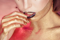 Studio Shot of a Golden Glittery Body Woman. Touching black lips. Purple Background stock photo
