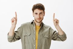 Studio shot of good-looking curly-haired guy with beard, posing over gray background with lifted index fingers, pointing. Up, smirking, hinting on something Royalty Free Stock Images