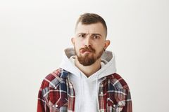 Studio shot of good-looking pierced urban male skater with stylish haircut and beard showing tongue, frowning, making stock photography