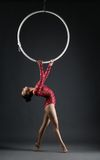 Studio shot of graceful acrobat performs with hoop Royalty Free Stock Photography