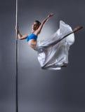 Studio shot of graceful woman turning around pole Royalty Free Stock Photography