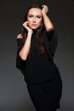 Studio shot of graceful young woman over dark Stock Photos