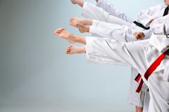 The studio shot of group of kids training karate martial arts. On gray backlground stock photography