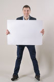 Studio shot of a handsome man in a suit holding up a blank sheet Stock Photo