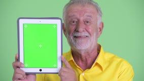 Face of happy senior bearded businessman showing digital tablet. Studio shot of handsome senior bearded businessman against chroma key with green background stock video