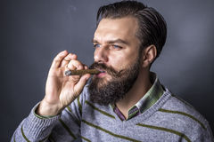 Studio shot of a handsome young man with retro look smoking a ci Stock Photos