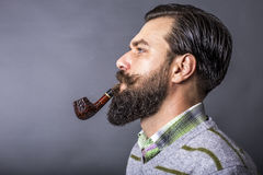 Studio shot of a handsome young man with retro look smoking pipe Royalty Free Stock Photo