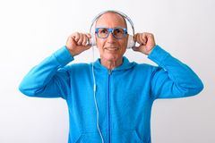 Studio shot of happy bald senior man smiling while listening to. Music and wearing eyeglasses against white background royalty free stock images