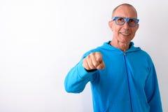 Studio shot of happy bald senior man smiling and pointing at cam. Era while wearing eyeglasses against white background stock photos
