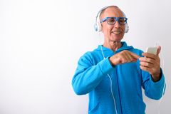 Studio shot of happy bald senior man smiling while using mobile. Phone and listening to music with eyeglasses against white background royalty free stock photography