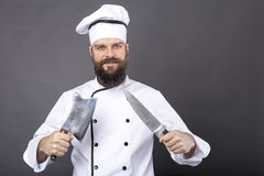 Studio shot of a happy bearded young chef holding sharp knives Stock Images